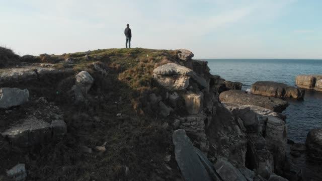 獨自站在海岸岩石上的人 - 懸崖 個影片檔及 b 捲影像