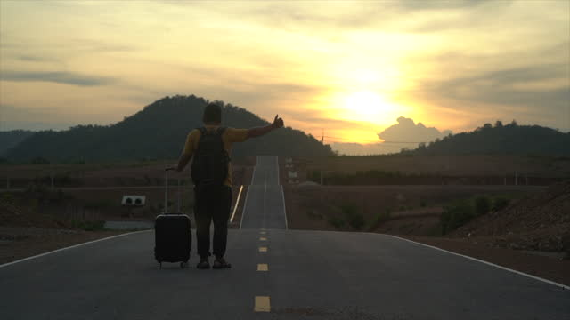 A man standing and hitchhiking on the road at the sunset.