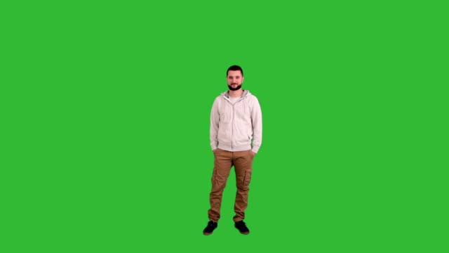 man standing and looking at the camera on a green background screen video