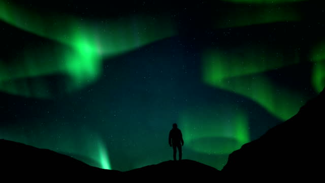 man standing and northern lights aurora borealis sky background - aurora boreale video stock e b–roll