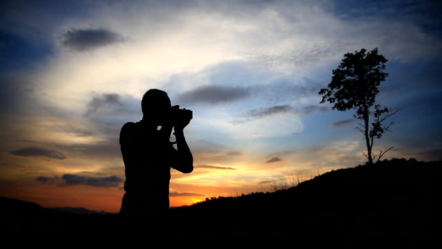 Man standing and taking pictures at suset. - vídeo