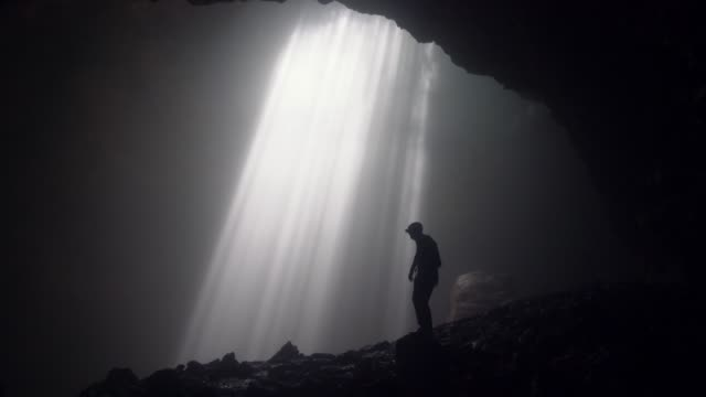 Man standing in Jomblan Cave in sunbeams
