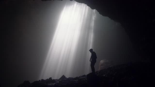 man standing in jomblan cave in sunbeams - geografia fisica video stock e b–roll