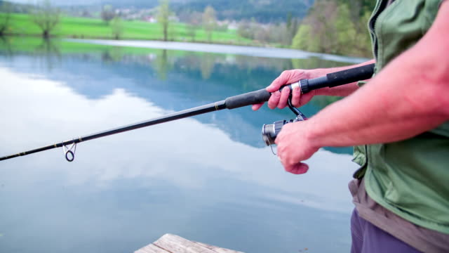 Man standing in the lake shore and winding the fishing line on a sunny day in a countryside, footage in slow motion. video