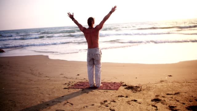 Man standing in yoga pose by the ocean at sunset video