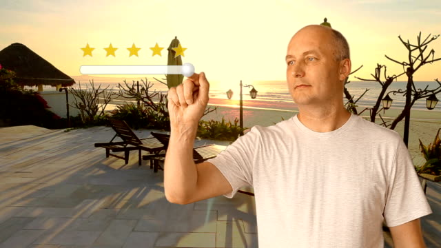 A man standing near the beach at sunset puts a rating of 5 stars for the resort. Virtual screen finger of a man's hand moves a button changing score. Gold stars are customer satisfaction. video