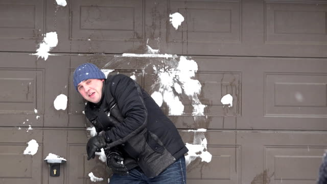 man standing near wall and someone throwing snow balls at him. snow falling video