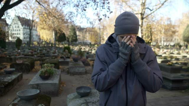 stockvideo's en b-roll-footage met mens staande op begraafplaats en diep huilen, ontbrekende verloren familie, eenzaamheid - funeral crying