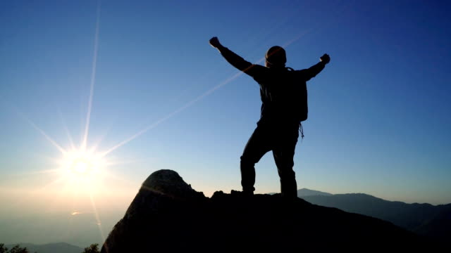 slo mo man standing on mountain and raising arms towards sunrise sky. - in cima video stock e b–roll