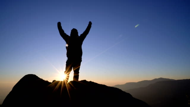 4K RT Man standing on mountain and raising arms towards sunrise sky.