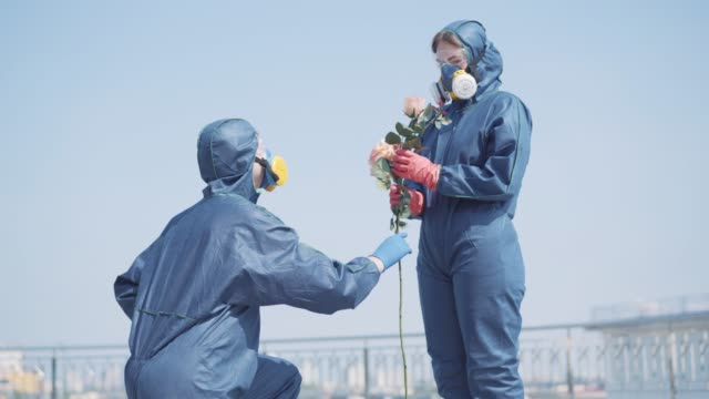 Man standing on one knee and giving flowers to woman in antiviral suit. Happy young Caucasian girl smelling bouquet and hugging boyfriend. Humor, dating on Covid-19 pandemic. Man standing on one knee and giving flowers to woman in antiviral suit. Happy young Caucasian girl smelling bouquet and hugging boyfriend. Humor, dating on Covid-19 pandemic. boyfriend stock videos & royalty-free footage
