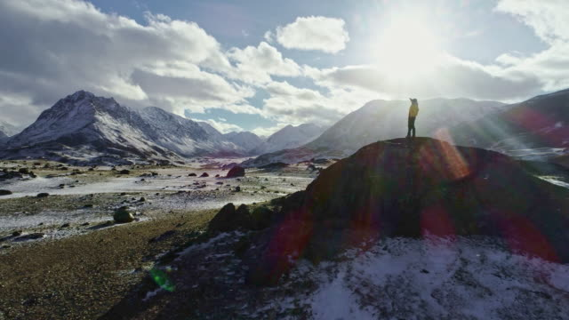 man standing on rock peak snowy winter mountain range achievement success outstretched arms happiness epic nature beauty vacation ski holiday concept - trekking sul ghiaccio video stock e b–roll