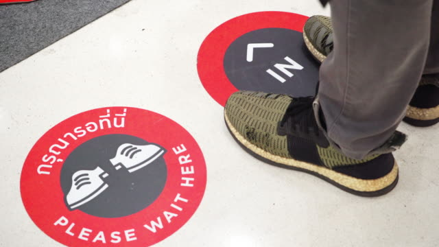 Man standing on Social distancing sign on the floor at a department store during the Covid-19 situation.