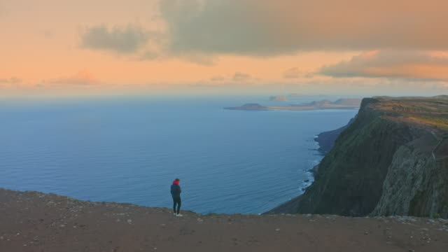 AERIAL WS Man standing on the edge of cliff and looking at the view at sunset / Canary Islands, Spain