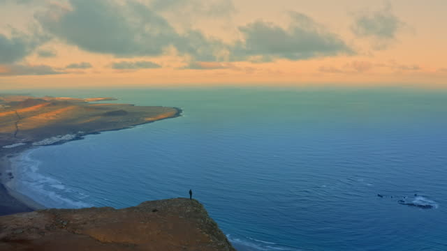 AERIAL WS Man standing on the edge of cliff at sunset / Canary Islands, Spain