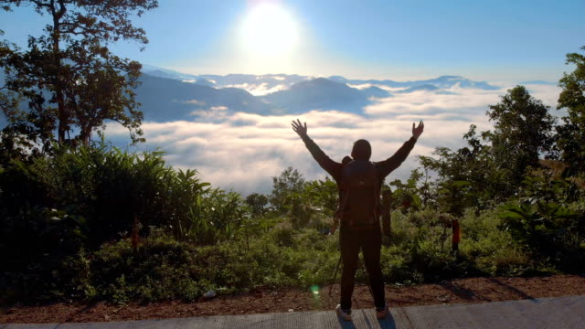 AERIAL Man standing on the mountain and raising his hands in morning sunrise