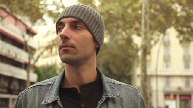 mann steht auf der straße und schaut sich um - kopfbedeckung stock-videos und b-roll-filmmaterial