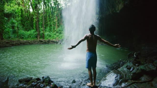 Man Standing Under Waterfall video