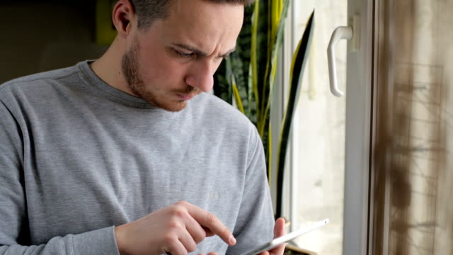 Man standing with tablet by the window at home video
