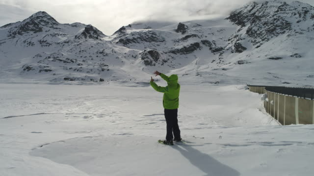 Man stands by frozen lake, makes frame with hands