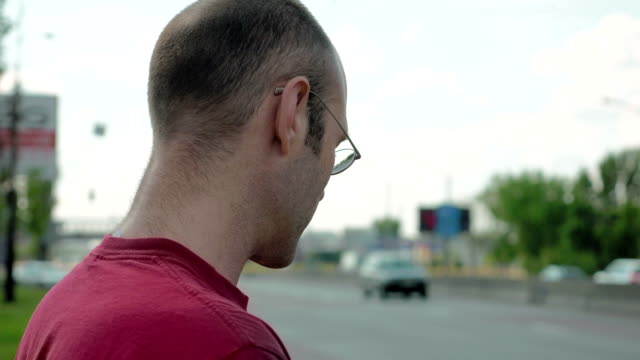 Man stands by roadside of city street traffic video