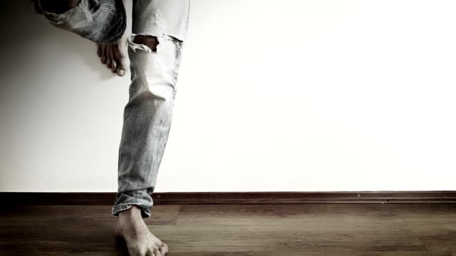 A man stands leaned towards the wall wearing ripped jeans and tapping with his foot video