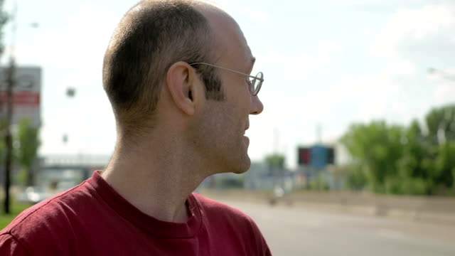 Man stands on roadside of city street traffic video