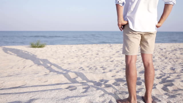 Man stands on the beach looking at the sea waves roll video