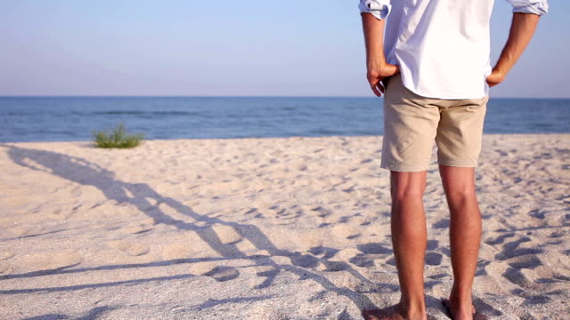 Man stands on the beach with hands on the waist video