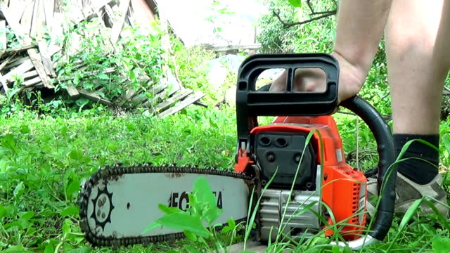 Man starts chainsaw on the outdoor video