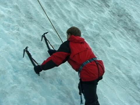 mann beginnt klettern einen gletscher wand - eisklettern stock-videos und b-roll-filmmaterial
