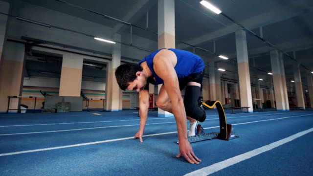 vídeos de stock e filmes b-roll de man starts to run on a track, wearing artificial leg, side view. - membro