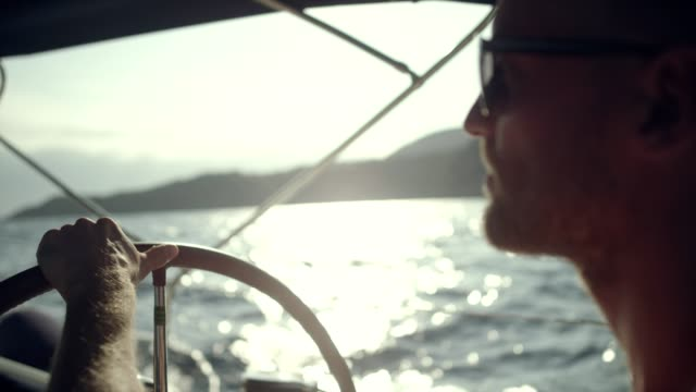 Man steers the yacht Active man sailing on sea. recreational boat stock videos & royalty-free footage