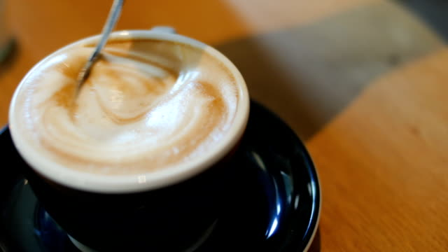 Man stirring sugar into coffee at coffee chop video