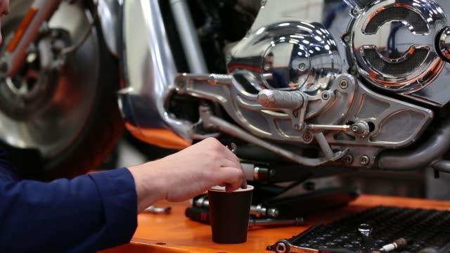 man stirs coffee with a wrench near the motorcycle in a workshop - klucz ręczne narzędzie filmów i materiałów b-roll