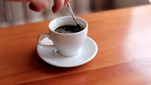 A man stirs sugar into a Cup of coffee. video