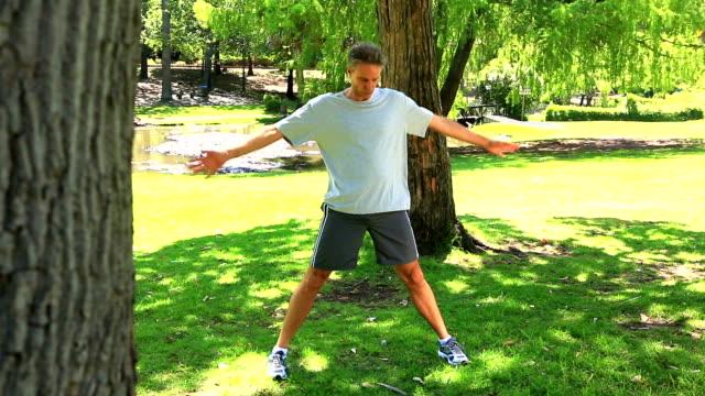 człowiek zaprzestaniu jego uruchom, aby rozciągnąć w parku - 50 54 lata filmów i materiałów b-roll