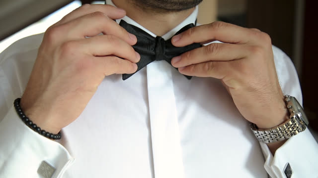 Man straightens his bow tie on white shirt Man straightens his bow tie on white shirt wristwatch stock videos & royalty-free footage
