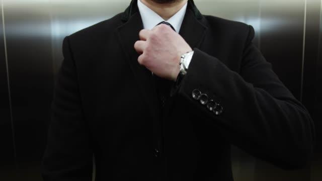 vídeos y material grabado en eventos de stock de hombre endereza la corbata en elevador - corbata