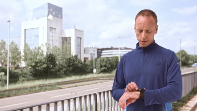 LD Man stretching and checking his watch before jogging video