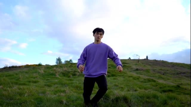 man snubblar och faller ner på gräs och rullar nedför backen - jogging hill bildbanksvideor och videomaterial från bakom kulisserna