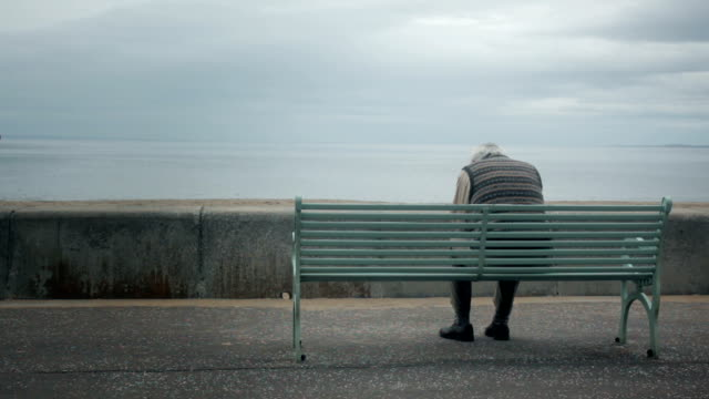 Man suffering by the sea An elderly man appears to be having some turmoil in his life as he sits at a bench by the sea, when a woman comes to comfort him. heterosexual couple stock videos & royalty-free footage