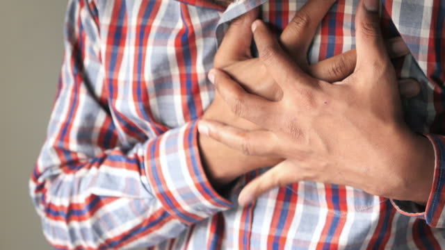 vídeos de stock e filmes b-roll de man suffering chest pain on gray background - artéria coronária