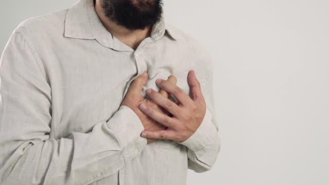 stockvideo's en b-roll-footage met man kramp of borst pijn lijden, ernstige hartaanval of pijnlijke krampen, druk op borst met pijnlijke expressie. - ongezond leven