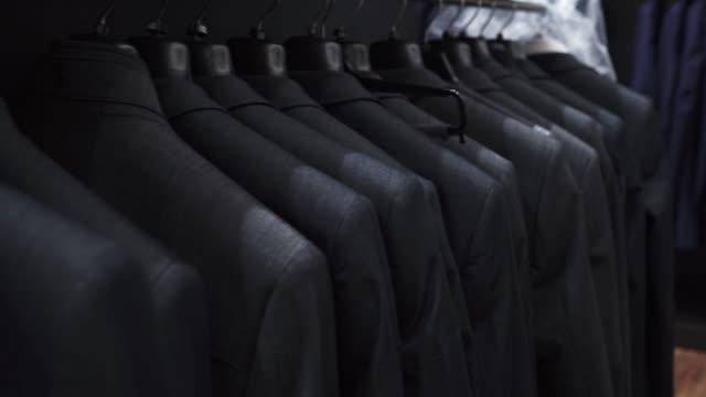 vidéos et rushes de l'homme s'adapte au magasin de vêtements - costume habillé
