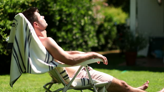 Man sunbathing outside in home lawn. Person outdoors relaxing Man sunbathing outside in home lawn. Person outdoors relaxing sunbathing stock videos & royalty-free footage