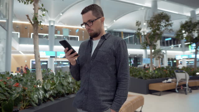 Man surfing net on mobile at airport lounge - vídeo