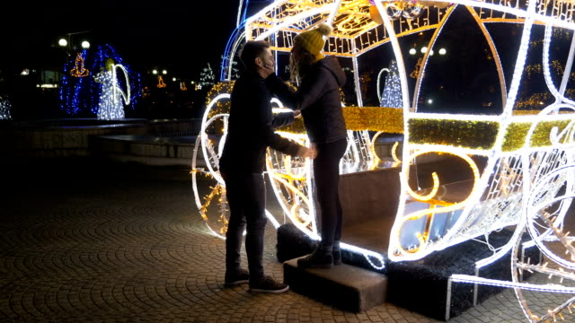 Man surprises his girlfriend with engagement ring at fair in a Christmas carriage decoration video