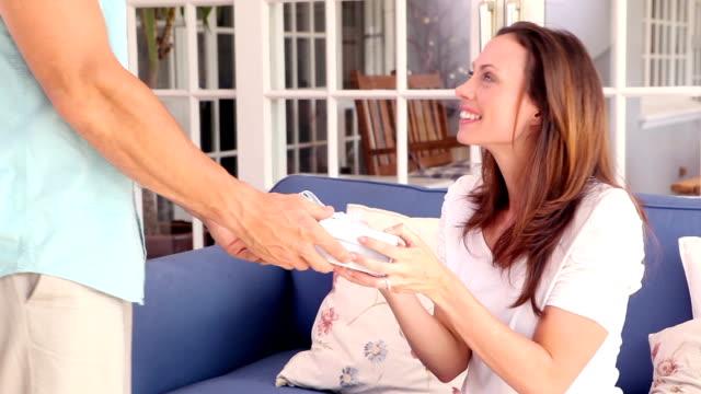 mężczyzna zaskakujące jego dziewczyna z prezent na kanapie - 30 39 lat filmów i materiałów b-roll