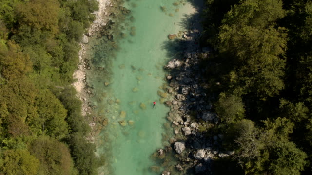 AERIAL: Man swimming down the crystal clear riverbed where people are kayaking video
